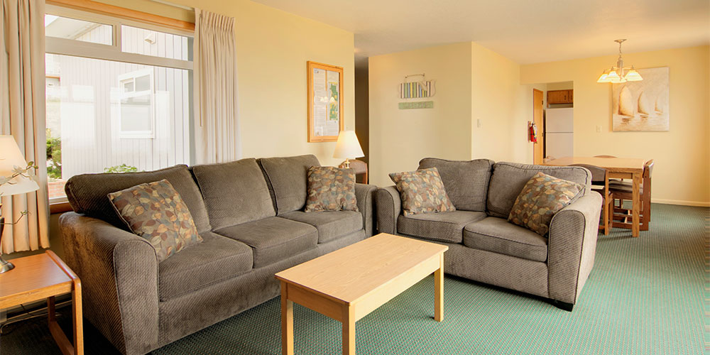 The living room is equipped with a large sofa, love seat, and coffee table.
