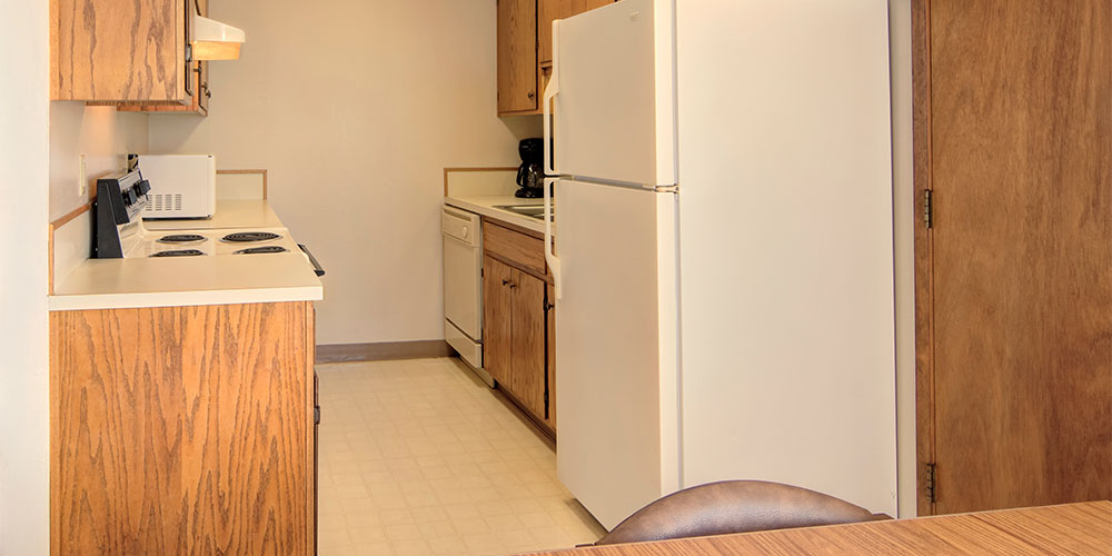 Kitchen with range, microwave, dishwasher, coffee pot and full-size refrigerator.