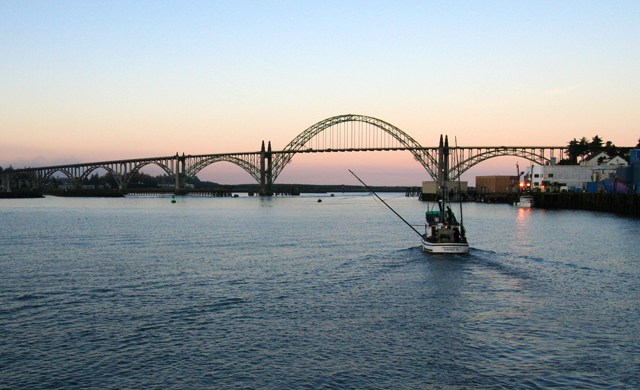 A fishing vessel heads towards Yaquina Bay Bridge at sunset